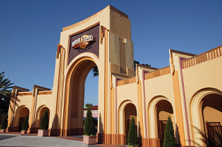 A regal, old Hollywood style arch that serves as the entrance to Universal Studios Florida, a theme park located in Orlando.